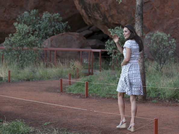 Catherine, Duchess of Cambridge waves to by standers as she walks along Kuniya walk at Uluru on April 22, 2014 in Ayers Rock, Australia. The Duke and Duchess of Cambridge are on a three-week tour of Australia and New Zealand, the first official trip overseas with their son, Prince George of Cambridge.