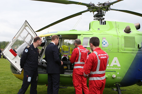 Prince William, Duke of Cambridge (2nd left) talks to Air Ambulance staff during a visit to Strathearn Community Campus on May 29, 2014 in Crieff, Scotland. The Duke and Duchess of Cambridge will spend the day in Scotland where they will tour a distillery and visit a village fete.