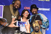 Music artists Biz Markie (L) and DJ Cool V (R) pose for a picture with a guest at EW & CNN The Eighties Trivia Event at The Django at the Roxy Hotel on March 29, 2016 in New York City.