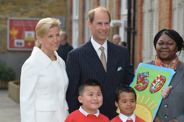 Prince Edward, Earl of Wessex, accompanied by his wife the Sophie, Countess of Wessex, watched by his wife the Countess of Wessex, is presented with a 50th birthday card by pupils John Lieu (L), nine, and Pharez Billy, seven, during an official visit on the Earl's 50th Birthday to Robert Browning Primary School in Walworth to see the work of youth charity Kidscape, recipients of grants from the Wessex Youth Trust, on March 10, 2014 in London, United Kingdom.