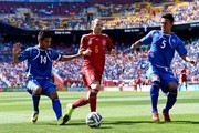 Andres Iniesta of Spain competes for the ball with Andres Flores (L) and Alexander Mendoza of El Salvador during an international friendly match between El Salvador and Spain at FedExField on June 7, 2014 in Landover, Maryland.