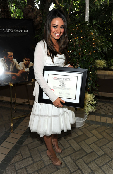 "Actress Mila Kunis poses with the ""Year of Excellance"" Award for ""Black Swan"" at the Eleventh Annual AFI Awards presentation at the Four Seasons Hotel on January 14, 2011 in Los Angeles, California."