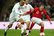 Wayne Rooney of England takes on Wael Gomaa (20) and Hossam Ghaly (12) of Egypt during the International Friendly match between England and Egypt at Wembley Stadium on March 3, 2010 in London, England.