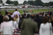 Racegoers watch the action from the open top buses as Paul Hanagan riding Imshivalla (C, red cap) win The Investec Wealth & Investment Stakes at Epsom Racecourse on June 3, 2016 in Epsom, England.