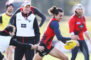 Jake Long of the Bombers runs with the ball past Bombers head coach John Worsfold during an Essendon Bombers AFL training session at The Hangar on July 26, 2018 in Melbourne, Australia.