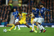 Wilfried Zaha of Crystal Palace is challanged by Andre Gomes of Everton and Seamus Coleman of Everton during the Premier League match between Everton FC and Crystal Palace at Goodison Park on October 21, 2018 in Liverpool, United Kingdom.
