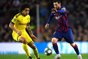 Lionel Messi of FC Barcelona runs with the ball under pressure from Axel Witsel of Borussia Dortmund during the UEFA Champions League group F match between FC Barcelona and Borussia Dortmund at Camp Nou on November 27, 2019 in Barcelona, Spain.