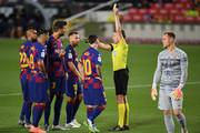 Gerard Pique of FC Barcelona is shown a yellow card by referee Alejandro Jose Hernandez Hernadez during the Liga match between FC Barcelona and Club Atletico de Madrid at Camp Nou on June 30, 2020 in Barcelona, Spain.