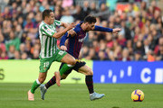 Lionel Messi of Barcelona is challenged by Andres Guardado of Real Betis during the La Liga match between FC Barcelona and Real Betis Balompie at Camp Nou on November 11, 2018 in Barcelona, Spain.