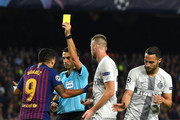 Luis Suarez of Barcelona is shown a yellow card by referee Ovidiu Hategan during the Group B match of the UEFA Champions League between FC Barcelona and FC Internazionale at Camp Nou on October 24, 2018 in Barcelona, Spain.