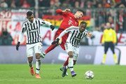 Robert Lewandowski of Bayern Muenchen collides with Patrice Evra of Juventus resulting in an yellow card to Lewandowski during the UEFA Champions League round of 16, second Leg match between FC Bayern Muenchen and Juventus at the Allianz Arena on March 16, 2016 in Munich, Germany.