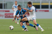 Alexis Sanchez of FC Internazionale is challenged by Daniele Dessena of Brescia Calcio during the Serie A match between FC Internazionale and Brescia Calcio at Stadio Giuseppe Meazza on July 1, 2020 in Milan, Italy.