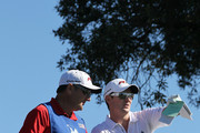 Justin Rose of England talks over his tee shot on the third hole with caddie Mark Fulcher during round one of the Farmers Insurance Open at Torrey Pines South Course on January 27, 2011 in La Jolla, California.