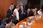 German Chancellor Angela Merkel (C, in white) and members of her government cabinet arrive for the first meeting of the new German government cabinet on March 14, 2018 in Berlin, Germany. Members of the new German government, a coalition between Christian Democrats (CDU/CSU) and Social Democrats (SPD), were sworn in today and will begin work immediately. The new government took the longest to create of any government in modern German history following elections last September that left the German Christian Democrats (CDU) as the strongest party but with too few votes in order to have a strong hand in determining the next coalition.