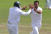 Imran Tahir  and Hashim Amla of South Africa celebrate the wicket of Thisara Perera of Sri Lanka during day 1 of the 1st Sunfoil Test match between South Africa and Sri Lanka at Supersport Park on December 15, 2011 in Pretoria, South Africa