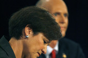 Florida Gubernatorial candidate, Democrat Alex Sink (L) takes notes during a debate with Republican Rick Scott (rear) on October 25, 2010 at the University of South Florida in Tampa, Florida. Sink is currently the Chief Financial Officer for the state of Florida. Scott is the former CEO of the healthcare company Columbia/HCA.