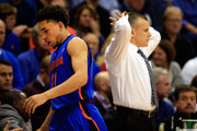 Chris Chiozza #11 of the Florida Gators passes head coach Billy Donovan on his way to the bench after coming off the floor late in the game against the Kansas Jayhawks at Allen Fieldhouse on December 5, 2014 in Lawrence, Kansas.