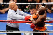 Referee Joe Cortez pulls Victor Ortiz off Floyd Mayweather Jr. as Ortiz is called for a minus point for a head-butt in the fourth round during their WBC welterweight title fight at the MGM Grand Garden Arena on September 17, 2011 in Las Vegas, Nevada.