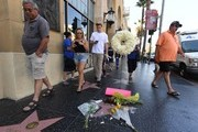 People walk past after flowers were placed on the Hollywood Walk of Fame star belonging to the Playboy Magazine founder Hugh Hefner, after he died aged 91, in Hollywood, California on September 28, 2017.  / AFP PHOTO / Mark RALSTON