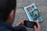 A fan photographs a newspaper showing a front page obituary of Hefner outside the Playboy Mansion home of Hugh Hefner, who was the founder of Playboy Magazine and has died aged 91, in Beverly Hills, California on September 28, 2017. .Hugh Hefner, the silk pajama-wearing founder of Playboy who helped escort nudity into the American mainstream, died Wednesday, the company announced. He was 91 years old..Hefner, father of the trailblazing brand that encouraged a loosening of sexual strictures, died of natural causes in his Los Angeles home -- the famed Playboy Mansion -- according to a statement from Playboy Enterprises.. / AFP PHOTO / Mark RALSTON