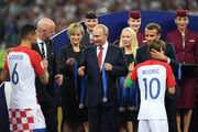 President of Russia Vladimir Putin presents Dejan Lovren and Luka Modric of Croatia with their medals next to FIFA president Gianni Infantino and French President Emmanuel Macron following the 2018 FIFA World Cup Final between France and Croatia at Luzhniki Stadium on July 15, 2018 in Moscow, Russia.