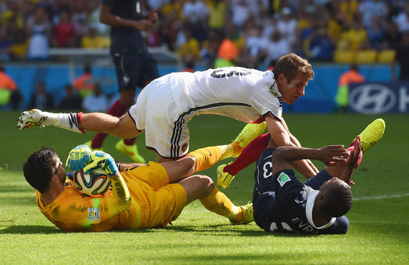 Thomas Mueller of Germany collides with Patrice Evra of France as goalkeeper Hugo Lloris of France makes a save during the 2014 FIFA World Cup Brazil Quarter Final match between France and Germany at Maracana on July 4, 2014 in Rio de Janeiro, Brazil.