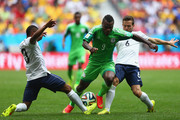 Emmanuel Emenike of Nigeria is challenged by Patrice Evra (L) and Yohan Cabaye of France during the 2014 FIFA World Cup Brazil Round of 16 match between France and Nigeria at Estadio Nacional on June 30, 2014 in Brasilia, Brazil.
