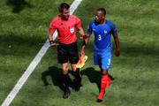 Patrice Evra of France talks to referee Nicola Rizzoli during the UEFA EURO 2016 round of 16 match between France and Republic of Ireland at Stade des Lumieres on June 26, 2016 in Lyon, France.