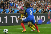 Adrian Popa of Romania is challenged by Patrice Evra of France during the UEFA Euro 2016 Group A match between France and Romania at Stade de France on June 10, 2016 in Paris, France.