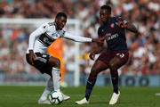 Andre-Frank Zambo Anguissa of Fulham battles for possession with Danny Welbeck of Arsenal during the Premier League match between Fulham FC and Arsenal FC at Craven Cottage on October 7, 2018 in London, United Kingdom.