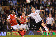 Matt Smith of Fulham is watched by Kirk Broadfoot of Rotherham United during the Sky Bet Championship match between Fulham and Rotherham United at Craven Cottage on April 15, 2015 in London, England.