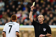 Match referee Mike Dean shows Steve Sidwell of Fulham the yellow card during the Barclays Premier League match between Fulham and Sunderland at Craven Cottage on January 11, 2014 in London, England.
