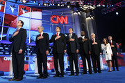 Republican presidential candidates (L-R) Rick Santorum, Rep. Ron Paul (R-TX), Texas Gov. Rick Perry, Mitt Romney, Herman Cain, Newt Gingrich, Rep. Michele Bachmann (R-MN), and Jon Huntsman listen to the national anthem prior to a debate at Constitution Hall November 22, 2011 in Washington, DC. The debate, hosted by CNN and in partnership with the Heritage Foundation and the American Enterprise Institute, was expected to focus primarily on national security, foreign policy and the economy.