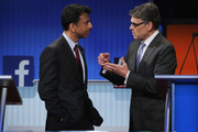 Republican presidential candidates Louisiana Gov. Bobby Jindal (L) and Rick Perry visit during a commercial break during a presidential pre-debate forum hosted by FOX News and Facebook at the Quicken Loans Arena August 6, 2015 in Cleveland, Ohio. Jindal, Perry and five other GOP candidates were selected to participate in the forum based on their rank in an average of the five most recent national political polls.