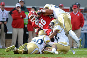 Lawrence Austin #20, Demond Smith #12 and Paul Davis #40 of the Georgia Tech Yellow Jackets tackle David Grinnage #86 of the North Carolina State Wolfpack during their game at Carter-Finley Stadium on November 8, 2014 in Raleigh, North Carolina.