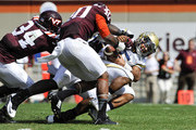 Quarterback Justin Thomas #5 of the Georgia Tech Yellow Jackets fumbles after being hit by linebacker Deon Clarke #40 and rover Kyshoen Jarrett #34 of the Virginia Tech Hokies in the second half at Lane Stadium on September 20, 2014 in Blacksburg, Virginia. The play had previously been blown dead for forward progress. Georgia Tech defeated Virginia Tech 27-24.