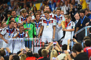 Philipp Lahm of Germany holds the World Cup trophy as teammates and head coach Joachim Loew look on during the 2014 FIFA World Cup Brazil Final match between Germany and Argentina at Maracana on July 13, 2014 in Rio de Janeiro, Brazil.