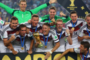 (L-R) Miroslav Klose, Philipp Lahm, Manuel Neuer, Erik Durm, Bastian Schweinsteiger, Ron-Robert Zieler, Toni Kroos, Julian Draxler and Thomas Mueller of Germany   celebrate with the World Cup trophy after defeating Argentina 1-0 in extra time during the 2014 FIFA World Cup Brazil Final match between Germany and Argentina at Maracana on July 13, 2014 in Rio de Janeiro, Brazil.