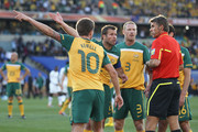 Harry Kewell (L), Lucas Neill  and Craig Moore of Australia argue with the referee Roberto Rosetti after he sends off Kewell for handball and awards Ghana a penalty during the 2010 FIFA World Cup South Africa Group D match between Ghana and Australia at the Royal Bafokeng Stadium on June 19, 2010 in Rustenburg, South Africa.