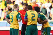 Craig Moore, Lucas Neill and Harry Kewell of Australia argue with the referee Roberto Rosetti after he sends off Kewell for handball and awards Ghana a penalty during the 2010 FIFA World Cup South Africa Group D match between Ghana and Australia at the Royal Bafokeng Stadium on June 19, 2010 in Rustenburg, South Africa.