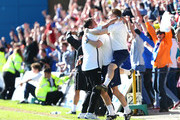 Martin Allen, Manager of Gillingham celebrates promotion with his assistants during the npower League Two match between Gillingham and AFC Wimbledon at Priestfield Stadium on April 20, 2013 in Gillingham, England.