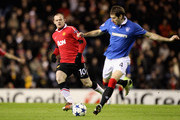 Kirk Broadfoot of Rangers is challenged by Wayne Rooney of Manchester United during the UEFA Champions League Group C match between Rangers and Manchester United on.