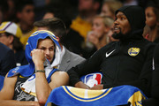 Stephen Curry #30 and Kevin Durant #35 of the Golden State Warriors react on the bench after a play against the Los Angeles Lakers during the first half at Staples Center on April 04, 2019 in Los Angeles, California. NOTE TO USER: User expressly acknowledges and agrees that, by downloading and or using this photograph, User is consenting to the terms and conditions of the Getty Images License Agreement.