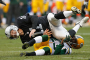 Kicker Sebastian Janikowski #11 of the Oakland Raiders is crashed into by Damarious Randall #23 of the Green Bay Packers in the first quarter at O.co Coliseum on December 20, 2015 in Oakland, California.