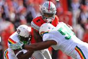 Braxton Miller #1 of the Ohio State Buckeyes is sandwiched between Trayvon Henderson #39 of the Hawaii Rainbow Warriors and Penitito Faalologo #54 of the Hawaii Rainbow Warriors in the first quarter at Ohio Stadium on September 12, 2015 in Columbus, Ohio.
