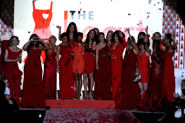 (L-R) Actress Felicity Huffman, singer Jordin Sparks, actresses Kristin Chenoweth, Raven-Symone, Kimora Lee, TV personality Bethenny Frankel, actress Regina King, Dara Torres, Kim Kardashian, actress Joan Collins, Heidi Klum, actresses Valerie Harper, Pauley Perrette, Elisabeth Hasselbeck, singer Estelle, and TV personality Robin RobertsA model walks the runway at the Heart Truth Fall 2010 Fashion Show during Mercedes-Benz Fashion Week at The Tent at Bryant Park on February 11, 2010 in New York City.