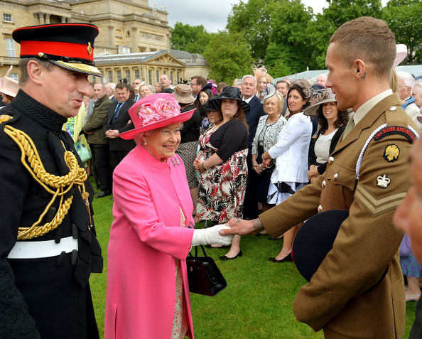 Queen Elizabeth II greets Corporal Sean Duffy of the Household Cavalry during a special Garden Party for the Regiment at  Buckingham Palace on May 28, 2014 in London, Untied Kingdom.