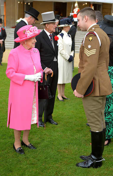 Queen Elizabeth II talks to Corporal of Horse Jamie Elliot (R) of the Household Cavalry, as the Prince Philip, Duke of Edinburgh and the Princess Anne, The Princess Royal meet other members during a special Garden Party for the Regiment on May 28, 2014 in London, Untied Kingdom.