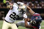 C.J. Spiller #28 of the New Orleans Saints is tackled by  Eddie Pleasant #35 of the Houston Texans at the Mercedes-Benz Superdome on August 30, 2015 in New Orleans, Louisiana.