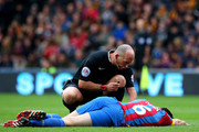 Referee Mike Dean speaks with Scott Dann of Crystal Palace as he lies injured on the pitch during the Barclays Premier League match between Hull City and Crystal Palace at KC Stadium on October 4, 2014 in Hull, England.